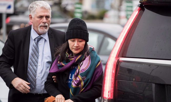 Huawei chief financial officer Meng Wanzhou arrives at a parole office with a member of her private security detail in Vancouver, on Dec. 12, 2018. (The Canadian Press/Darryl Dyck)