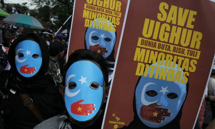 Protesters, who are members of the Muslim Solidarity Movement, hold placards during a protest against violence and the treatment of Uyghur Muslims by the Chinese regime, in Bandung, West Java, Indonesia on Dec. 21, 2018. (Antara Foto/Novrian Arbi/via Reuters)