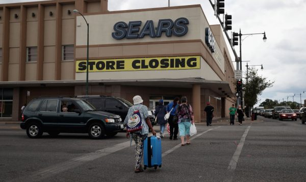 A sign announcing the store will be closing hangs above a Sears store