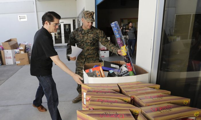Sgt. Christian Pastrana, right, prepares toys for a donation to the organization Women in Distress, at the Marine Corps Toys for Tots depot in Hialeah, Fla., on Dec. 19, 2018. (Lynne Sladky/AP Photo)