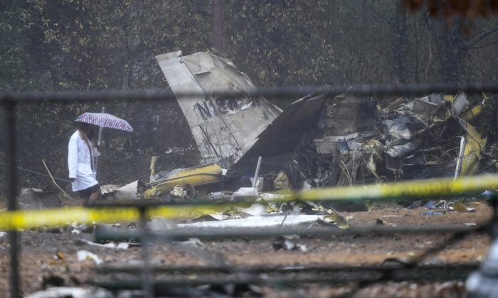 A person investigates the scene of a small plane crash in a city park which killed all on board in northwest Atlanta, on Dec. 20, 2018. (John Amis/AP Photo)