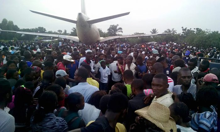 People gather around an Airbus A310 cargo jet that overshot the runway while landing  in the central city of Mbuji-Mayi, Congo, killing seven residents with homes adjacent the airport on Dec. 24, 2015. (Stringer/AFP/Getty Images)