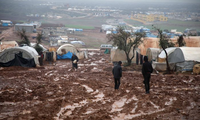 Syrian displaced people walk in a flooded camp near Kah, in the Idlib province, northeastern Syria, on Dec. 19, 2018. (Aaref Watad/AFP/Getty Images)