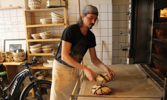 Maxime Bussy, owner and founder of Le Bricheton bakery in Paris, takes peasant chestnut bread out of the oven. (Alexia Luquet/Special to The Epoch Times)
