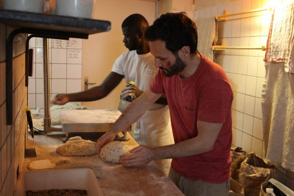 Another baker working with assistant to round the dough