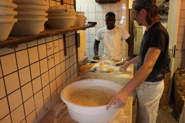 The french baker bussy working with dough with his assistant