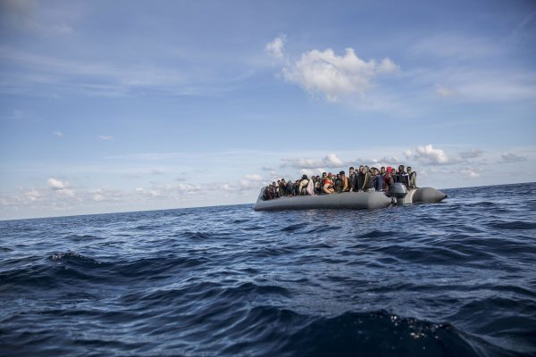 Migrants sit in rubber dinghy