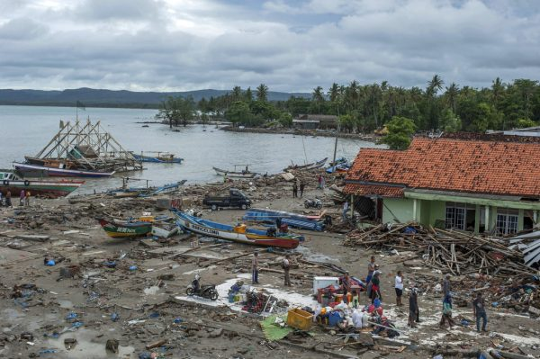 People inspect the damage at a tsunami-ravaged village in Sumur