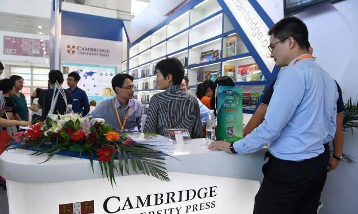 People at the Cambridge University Press stand at the Beijing International Book Fair in Beijing on Aug. 23, 2017. Just days after an outcry over an attempt to censor a British academic journal in China, hundreds of international publishing houses are courting importers at a major book fair in Beijing. (Greg Baker/AFP/Getty Images)