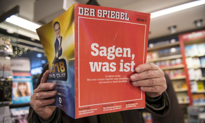 "A man looks into the latest issue of German newsweekly Der Spiegel with a cover page that reads, ""To say, what is"" in Cologne, Germany, on Dec. 22, 2018. (Thomas Lohnes/Getty Images)"