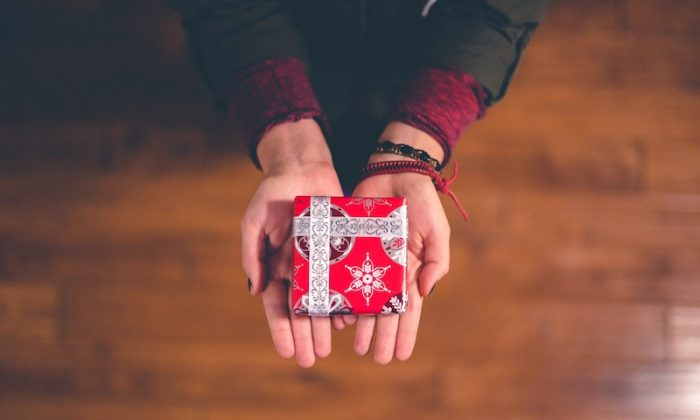 A person offering a gift. (Ben White/Unsplash)