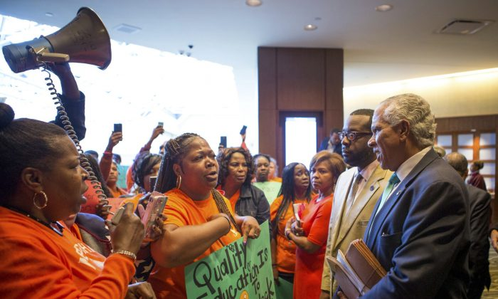 Parents and grandparents from Memphis Lift speak to Hilary Shelton, the Director to the NAACP's Washington Bureau and Senior Vice President for Advocacy and Policy, during the national NAACP board meeting in downtown Cincinnati on Oct. 15, 2016. (The Cincinnati Enquirer via AP)