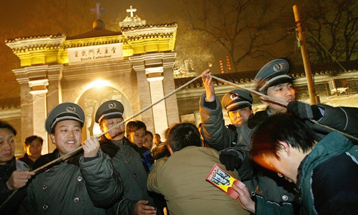 Chinese Catholics walk through security checkpoint outside a government approved Catholic church in Beijing, Dec. 24, 2007, for the Christmas mass. (©Getty Images | TEH ENG KOON/AFP)
