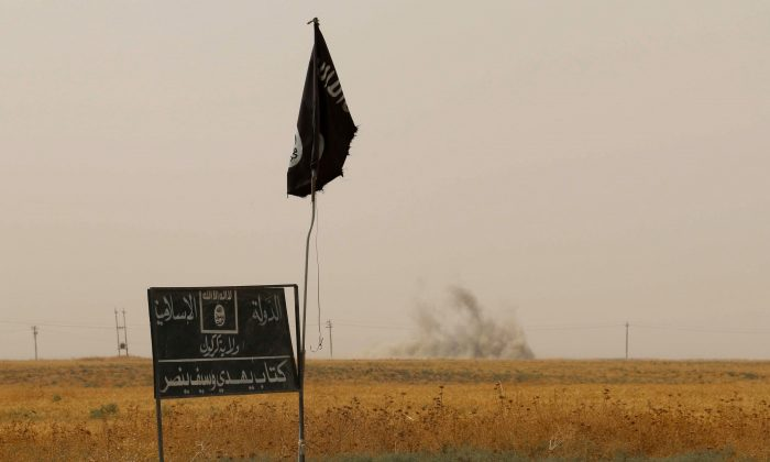 Smoke rises in the distance behind an ISIS flag and banner after Iraqi Kurdish Peshmerga fighters reportedly captured several villages from ISIS in Daquq District, Iraq, on Sept. 11, 2015. (Marwan Ibrahim/AFP/Getty Images)