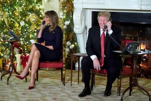President Trump and the first lady participate in NORAD Santa tracker phone calls from children, in the State Dining Room of the White House in Washington