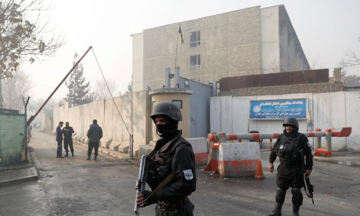 File—Afghan policemen outside a government compound in Kabul that was hit by an attack on Dec. 25, 2018. The Jan. 20, 2019, car bomb blast on a highway near Kabul targeted a convoy, killing at least eight Afghan security force members. (Mohammad Ismail/Reuters)