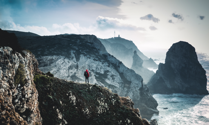 """Walking on the edge of the land on a cloudy day, the ocean with big waves against the """"walls"""". (Unsplash)"""