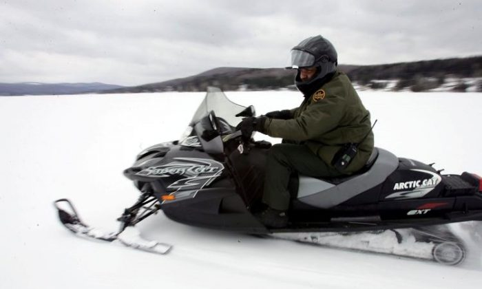 A U.S. Border Patrol agent rides a snowmobile on a frozen lake near the Vermont-Quebec border in a file photo. (Joe Raedle/Getty Images)