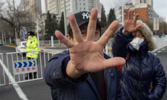 Plainclothes police officers gesture to stop photographs from being taken in front of the number 2 intermediate people's court in Tianjin on December 26, 2018, where the trial of human rights lawyer Wang Quanzhang is set to begin. (NICOLAS ASFOURI/AFP/Getty Images)