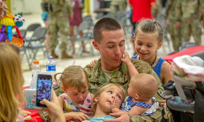 A soldier with the 25th Aviation Regiment embraces his family at a ceremony honoring the troops prior to their deployment at Wheeler Army Airfield, Hawaii, on June 5, 2018. Researchers hope neurofeedback training can help soldiers better deal with the stress of warfare. (U.S. Army photo by Sgt. Ian Morales)