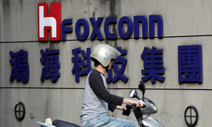 A motorcyclist rides past the logo of Foxconn, the trading name of Hon Hai Precision Industry, in Taipei, Taiwan on March 30, 2018. (Tyrone Siu/Reuters)