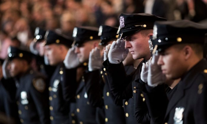 The newest members  of the New York City Police Department (NYPD) salute during their police academy graduation ceremony at the Theater at Madison Square Garden, March 30, 2017 in New York City. (Drew Angerer/Getty Images)