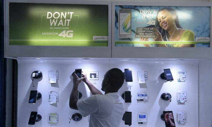 An employee arranges a display of smartphones at a Safaricom shop in Nairobi, Kenya, on Nov. 22, 2018. Chinese telecoms giant Huawei has partnered with Safaricom to roll out 4G networks. (SIMON MAINA/AFP/Getty Images)