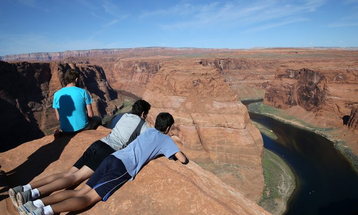 People lie on the edge of a cliff to view the Colorado River at Horseshoe Bend on March 30, 2015, in Page, Arizona. (Justin Sullivan/Getty Images)