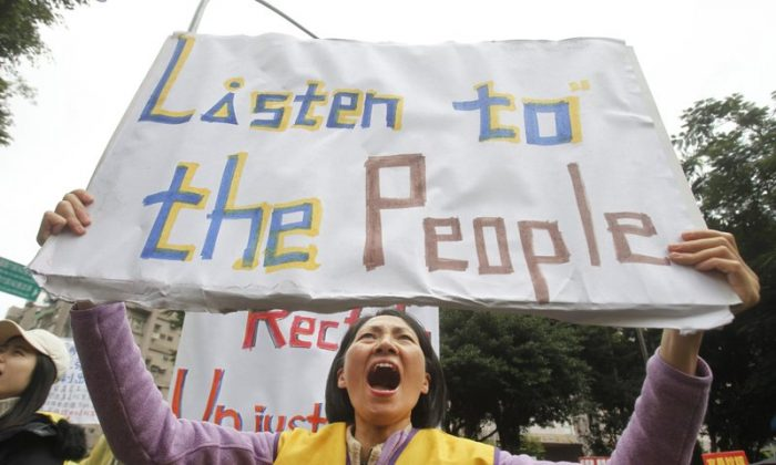 A protester shouts slogans demanding tax reform outside the Ministry of Finance in Taipei, Taiwan, on Dec. 27, 2018. (AP Photo/Chiang Ying-ying)