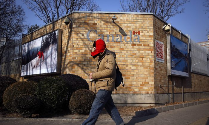 A man walks by the Canadian Embassy in Beijing, on Dec. 14, 2018. (AP Photo/Andy Wong)