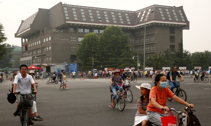 People cycle past a building in Peking University in Beijing, China on July 27, 2016.  (Thomas Peter/Reuters)