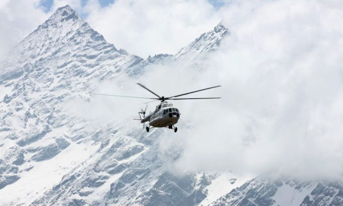 A Russian helicopter flies past Mount Thamserku in Syangboche, Nepal, on April 6, 2018. (AP Photo/Tashi Sherpa)