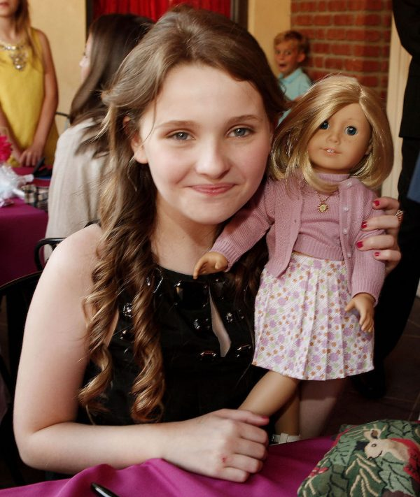 Girl poses with American girl doll.
