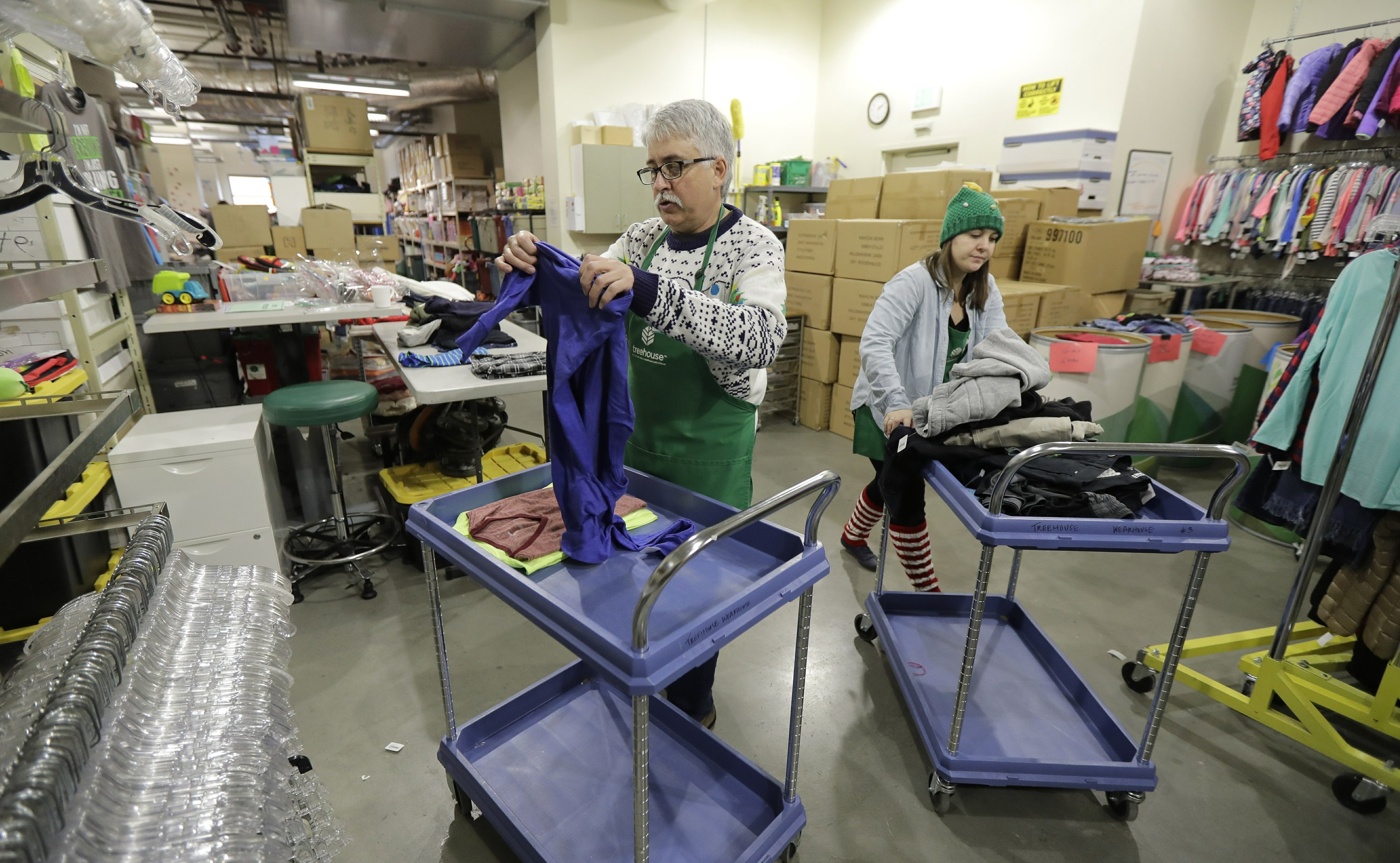 Chris Meyer, left, and Maddi Heim, fold and sort donated clothes at Treehouse, a nonprofit organization in Seattle that serves the needs of children in the foster-care system. The charity was one of several that received donations from the $11 million secret estate of Alan Naiman -- a social worker who died from cancer earlier in 2018 after living a private life of frugality and concern for children facing hardship. Dec. 21, 2018. (Ted S. Warren/AP)