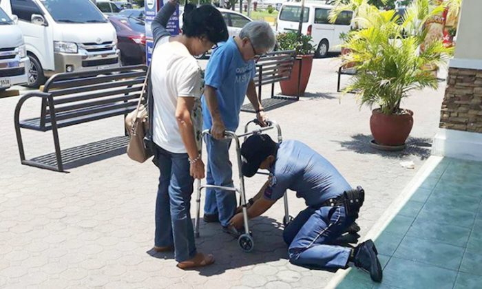 Filipino police officer assisting an elderly couple in the parking lot. (Facebook | PNP Good Deeds)