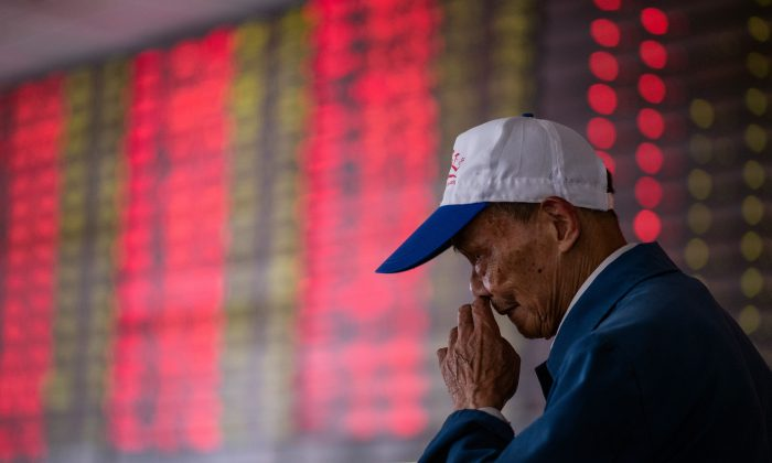 An investor looks at an electronic board showing stock information at a brokerage house in Shanghai Oct. 15. (Johannes Eisele/AFP/Getty Images)