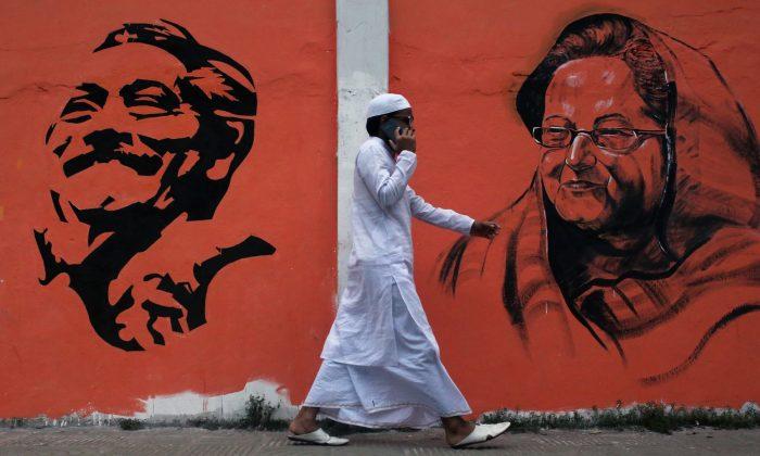 A man walks past a wall with images of Bangladeshi founding father Sheikh Mujibur Rahman (L) and Prime Minister and leader of Awami League (AI), Sheikh Hasina Wazed (R) as general election campaigns take place in Dhaka on December 16, 2018. (REHMAN ASAD/AFP/Getty Images)