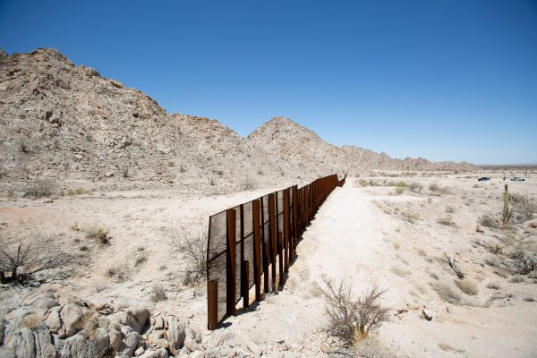The U.S.–Mexico border where the fence ends at the side of a rocky mountain in the desert near Yuma, Ariz., on May 25, 2018. The United States is on the right side of the fence. (Samira Bouaou/The Epoch Times)