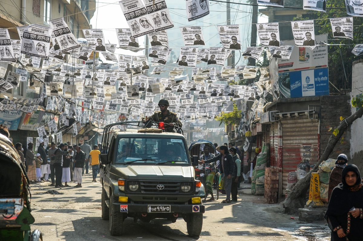 Bangladeshi army personnel drive a military vehicle through a street adorned with election posters near a polling station in Dhaka on Dec. 30, 2018. (Munis Uz Zaman/AFP/Getty Images)