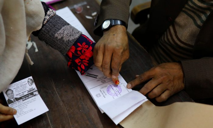 A presiding officer places a voter's thumbprint on the ballot paper before she casts her vote for the general election in Dhaka, Bangladesh, on Dec. 30, 2018. (Mohammad Ponir Hossain/Reuters)