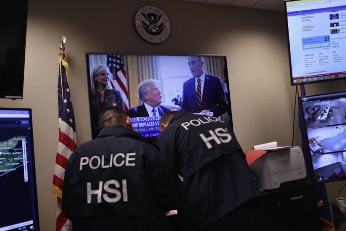 Homeland Security Investigations ICE agents work in control center.