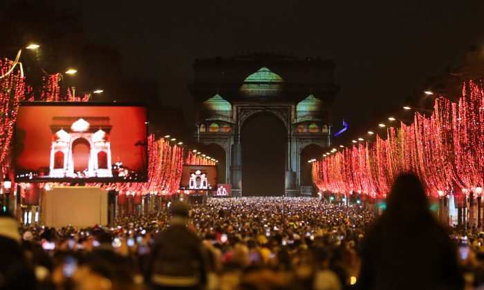 Revellers gather near the illuminated Arc de Triomphe on the Champs-Elysees for New Year's celebrations in the French capital Paris on Dec. 31, 2018. (Zakaria Abdelkafi/AFP/Getty Images)