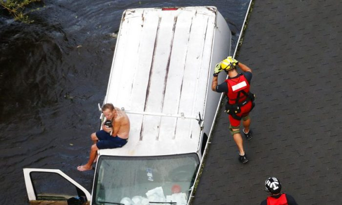 U.S. Coast Guard rescue swimmer Samuel Knoeppel, center, and Randy Haba, bottom right, approach to Willie Schubert of Pollocksville, N.C., on a stranded van during Hurricane Florence in Pollocksville on Sept. 17, 2018. (AP Photo/Steve Helber)