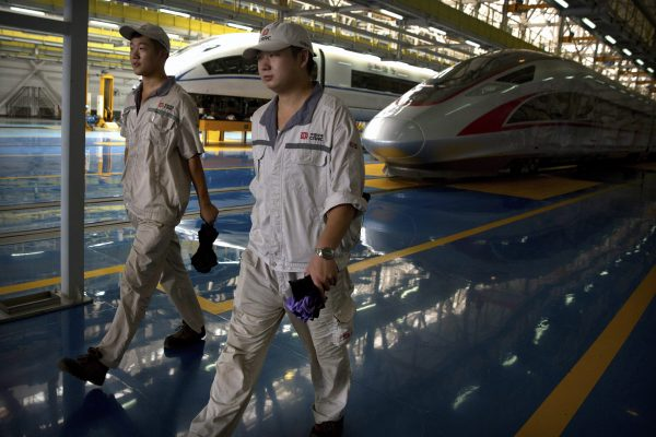 workers walk alongside the high speed trains