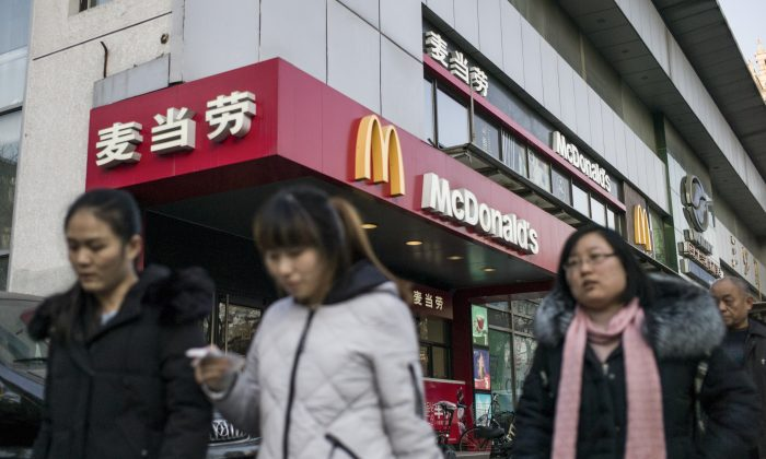 People walk past a McDonald's fast food restaurant in Beijing. (FRED DUFOUR/AFP/Getty Images)