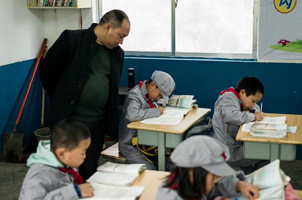 "This photo taken on November 7, 2016 shows a teacher supervising students in the Yang Dezhi ""Red Army"" elementary school in Wenshui, Xishui country in Guizhou province. 