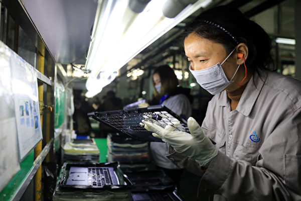 Workers check laptop parts in a factory in the Hangyong Auto Industrial Park, in Lu'an City, Anhui Province, China. The factory produces equipment for Toshiba, Matsushita and other international brands. (STR/AFP/Getty Images)