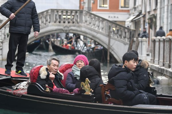 A group of tourists sits on a gondola sailing on a canal of Venice