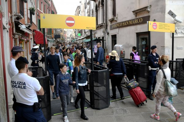 Venice's citizens and tourists pass through turnstiles