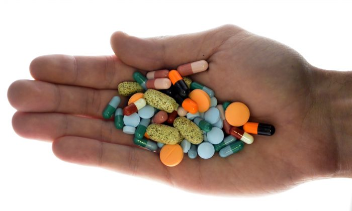 A person holds pharmaceutical tablets and capsules in this picture illustration taken in Ljubljana Sept. 18, 2013. (REUTERS/Srdjan Zivulovic
